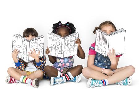 Little Children Reading Sitting Down Imagens