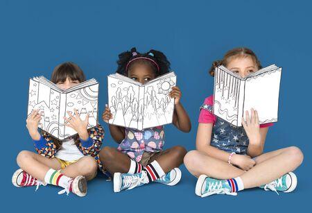 storybook: Little Children Reading Sitting Down Stock Photo