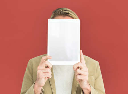 Man Holding Up Tablet Covering Face Stock Photo