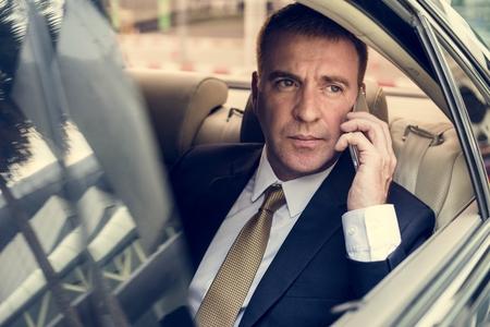 Zakenman praten met behulp van telefoon auto binnen Stockfoto