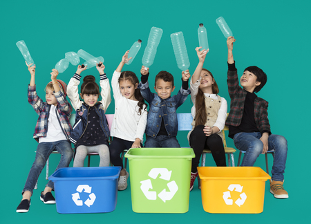 Kids and plastic bottles in a recycle bin Imagens - 76141351
