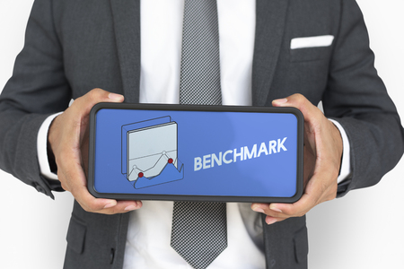 Businessman holding a mobile phone wih benchmark concept