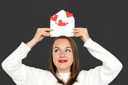 Woman holding envelope red paper hearts Stock Photo
