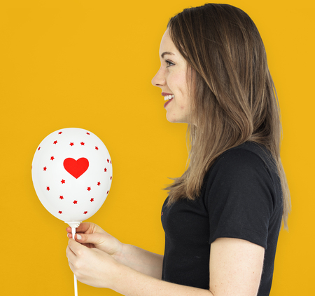 dimple: Young girl smiling holding a balloon
