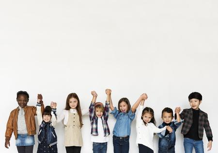 白い Blackground に笑みを浮かべて手顔式幸福を保持している子供のグループ 写真素材