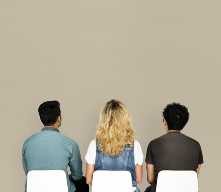 Rear view of three people sitting with copy space