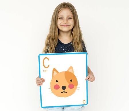 Happiness little girl smiling and holding alphabet animal placard Stock Photo