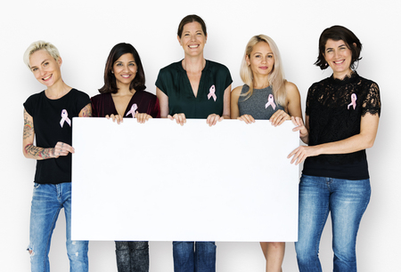 Group of women with pink ribbon and holding blank banner for breast cancer awareness Stock Photo - 76395589