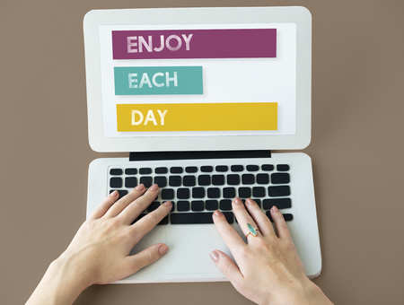Woman using a laptop with the words Enjoy Each Day