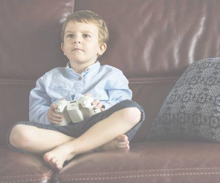 jugando videojuegos: Niño de vacaciones jugando juego sentado en el sofá en su casa