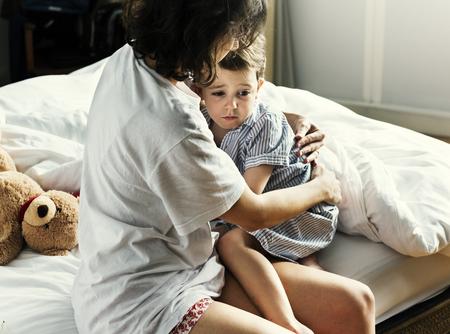 Mère câlin et consolant le petit garçon de cauchemar Banque d'images