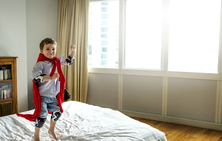 Playful superhero little boy jumping on the bed