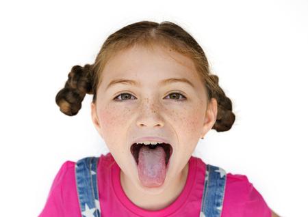 Felicità sorridente della bambina che attacca fuori il ritratto dello studio della lingua Archivio Fotografico - 76472067