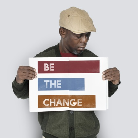 African man showing a placard with the words Be The Change Stok Fotoğraf