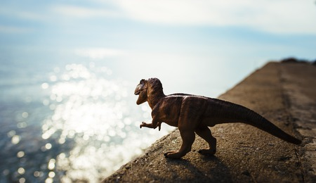 T Rex Dinosaur Toy Model Standing Next To Ocean Stock Photo