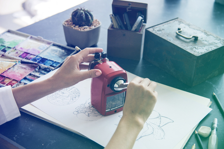 sketchpad: Woman Sharpen Pencil On A Black Table Stock Photo