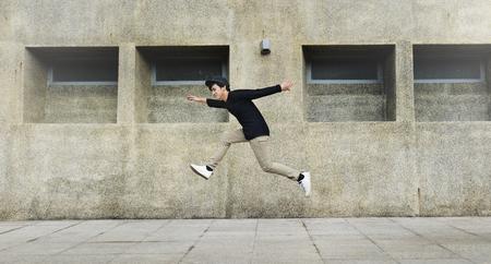 若い男が大学キャンパスの建物のフロントにジャンプ 写真素材