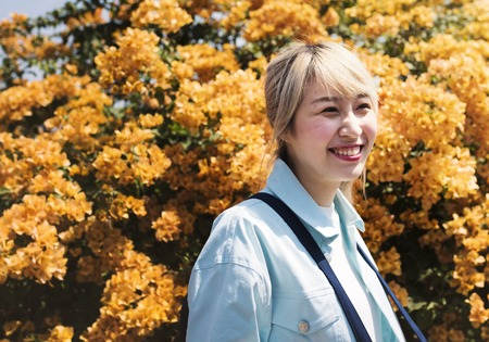 Adult Asian Woman Stadning with Yellow Bougainvillea Flower Stock Photo