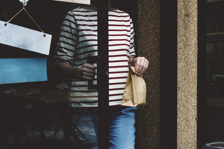 Adult Woman Exiting Door with Paper Bag in Hand