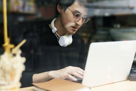 Young asian boy wearing hoodie using digital laptop