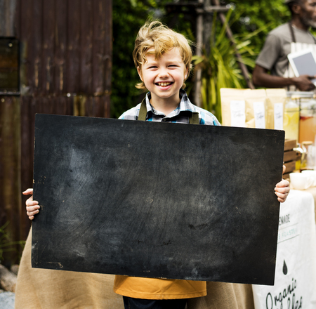 Boy holding copyspace blackboard at farmers market festival