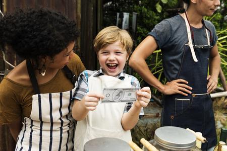 Happiness little boy earn the money from selling lemonade