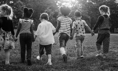 Groep kleuterschool kinderen vrienden houden handen spelen op park