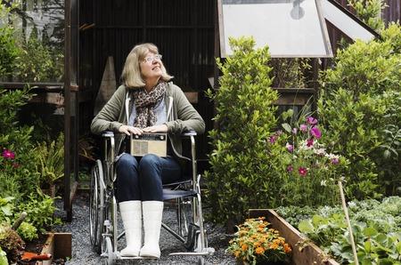庭で車椅子にシニアの大人の女性