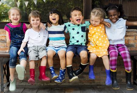 유치원 아이들의 그룹 친구 팔 앉아서 웃고 주위에 재미