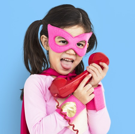 Young girl dressed up in a pink superhero costume