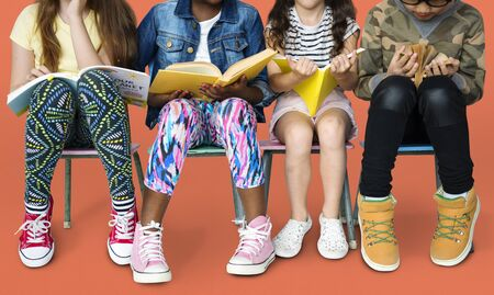 Diverse group of kids sitting in a row reading books 版權商用圖片 - 76715483