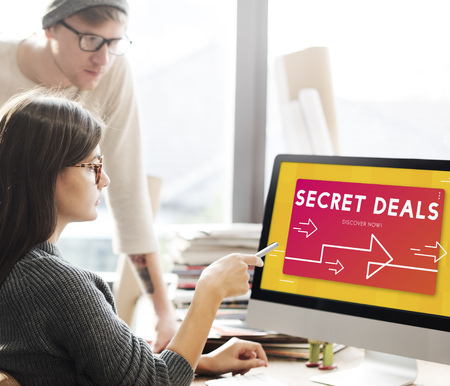 People looking at computer screen with secret deal concept