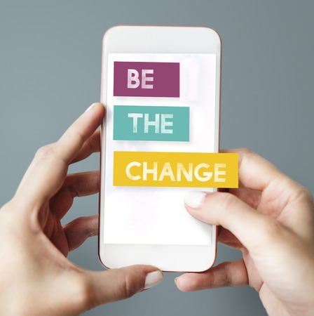 Woman using a mobile phone with the word Be The Change