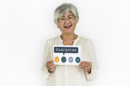 Cheerful senior woman holding a card with guarantee concept Stockfoto