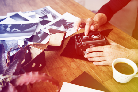 habitual: photographer hands cleaning camera lens on wooden table