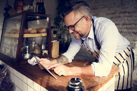 Man using devices for online business order at bakehouse 版權商用圖片 - 76929176