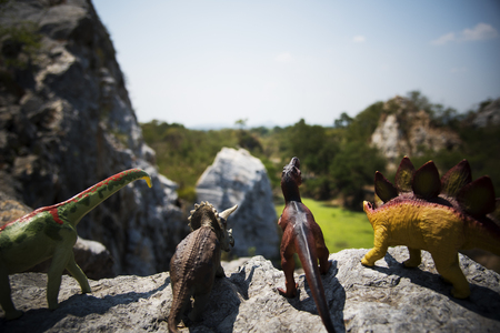 Dinosaur figure toy on the top of mountain