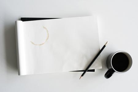 白いテーブルの上にコーヒー カップの鉛筆スケッチ パッド 写真素材