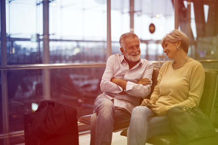 Senior couple waiting for boarding inside airport