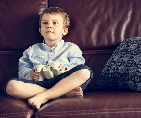 jugando videojuegos: Boy Holiday Playing Game Sitting on Sofa at His Home