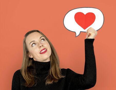 Woman holding speech bubble heart