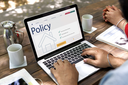 Person using a laptop with policy concept