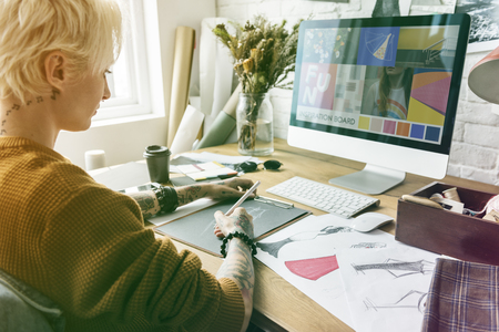 workroom: Fashion designer tattooed girl drawing cloth pattern