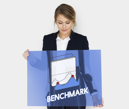 Businesswoman holding a board with benchmark concept Standard-Bild