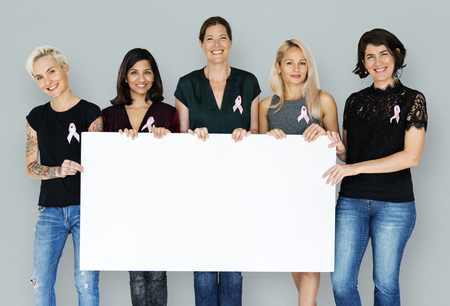 Group of women with pink ribbon and holding blank banner for breast cancer awareness
