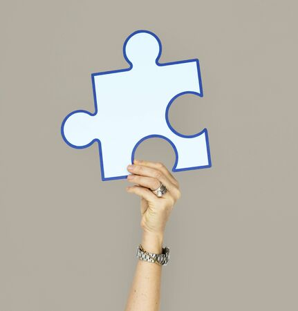 Human Hand Holding Puzzle Piece