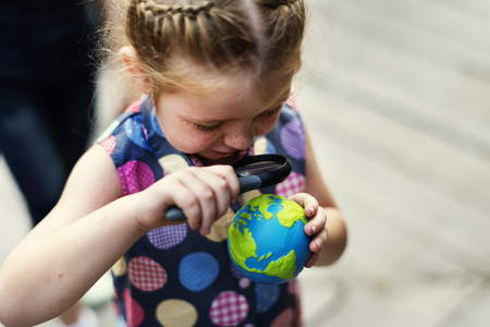 A girl is using magnifier take a look at the planet ball