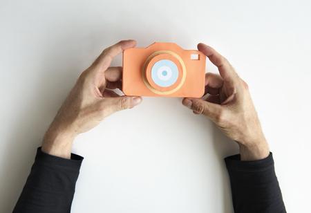 カメラのデザインを保持しているペーパー クラフトの人