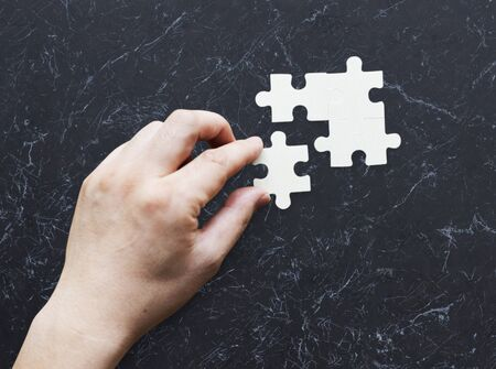hand holding paper: Togetherness Connection Teamwork Jigsaw Game