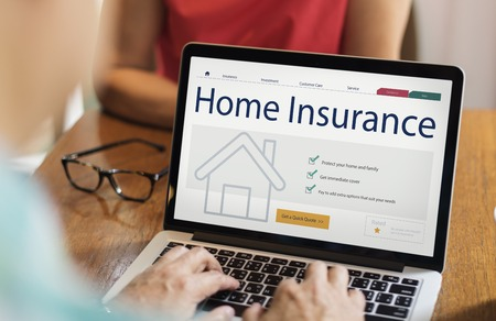 Person using a laptop with home insurance concept